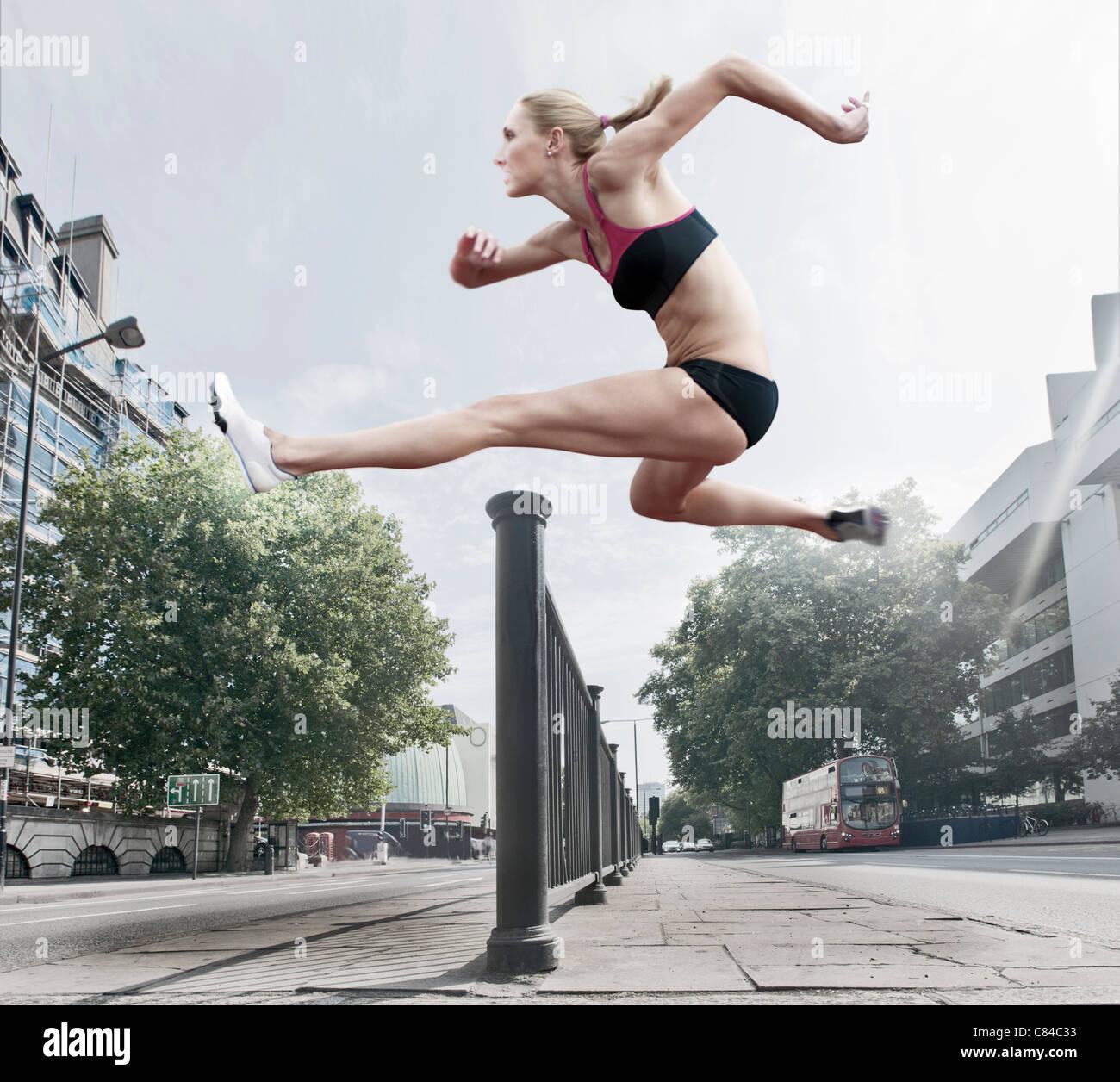 Atleta saltando por Bannister en la calle Imagen De Stock