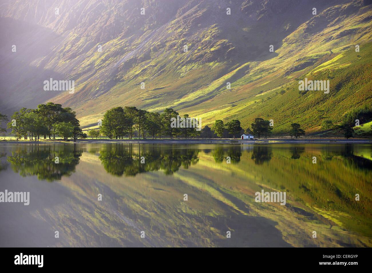 Reflexiones sobre la orilla de Buttermere al amanecer, Cumbria, distrito de Los Lagos, Cumbria, Inglaterra, Reino Imagen De Stock