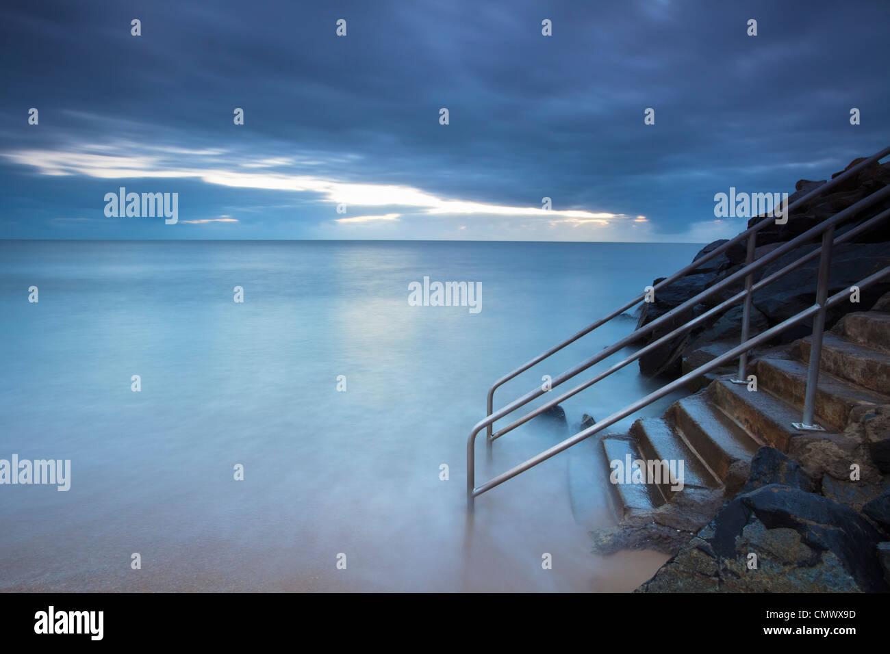 Olas lavando más pasos que conducen al mar. Machans Beach, Cairns, Queensland, Australia Imagen De Stock