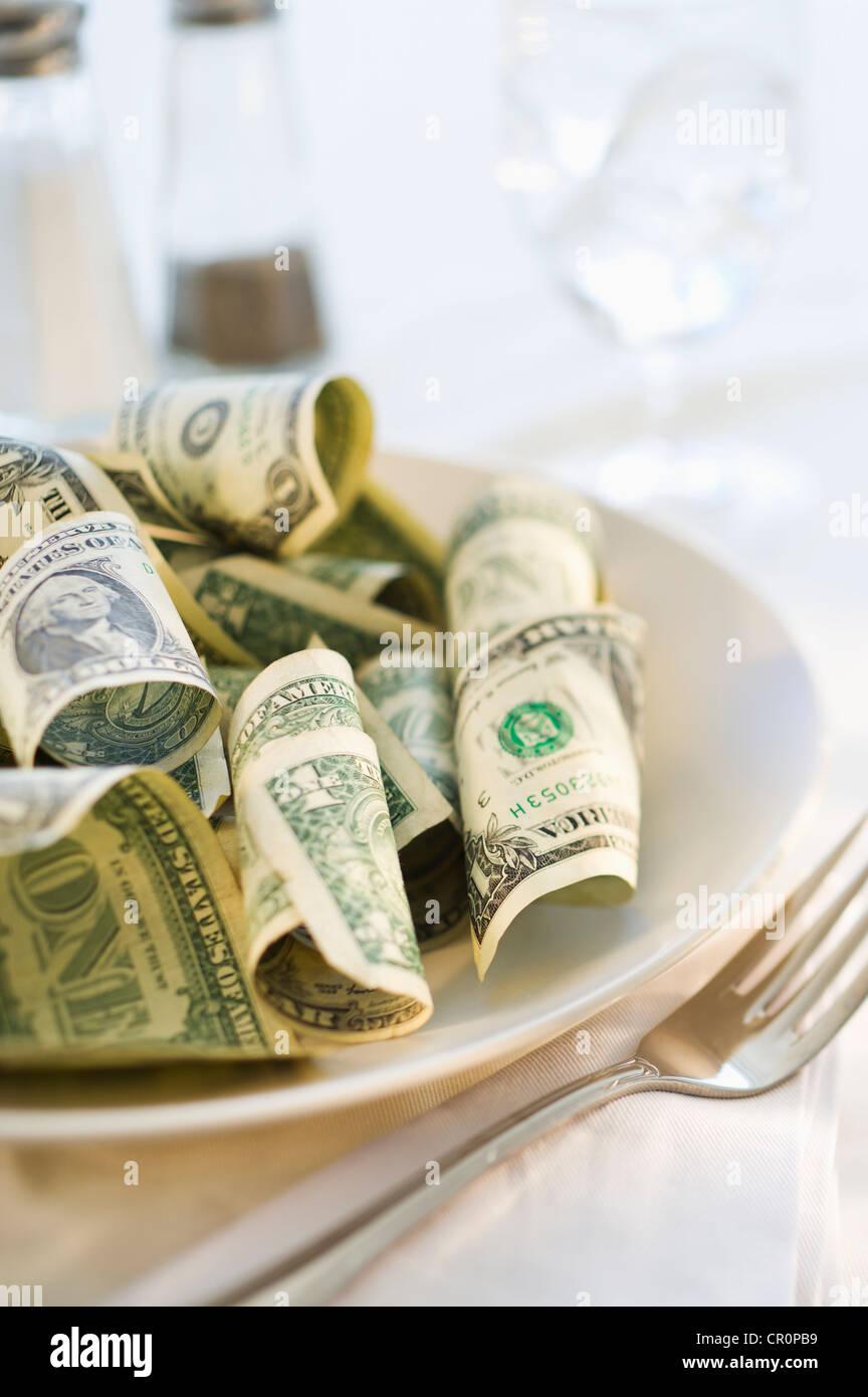 El papel moneda en el plato de comida, Foto de estudio Imagen De Stock