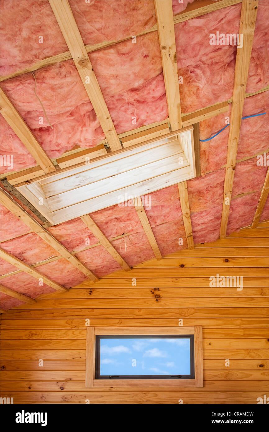 Aislamiento de fibra de vidrio instalado en la viguería de madera de una casa. Imagen De Stock