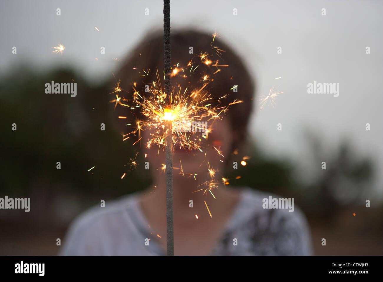 Chico de 13 años sostiene una gran spakler el 4 de julio. Imagen De Stock