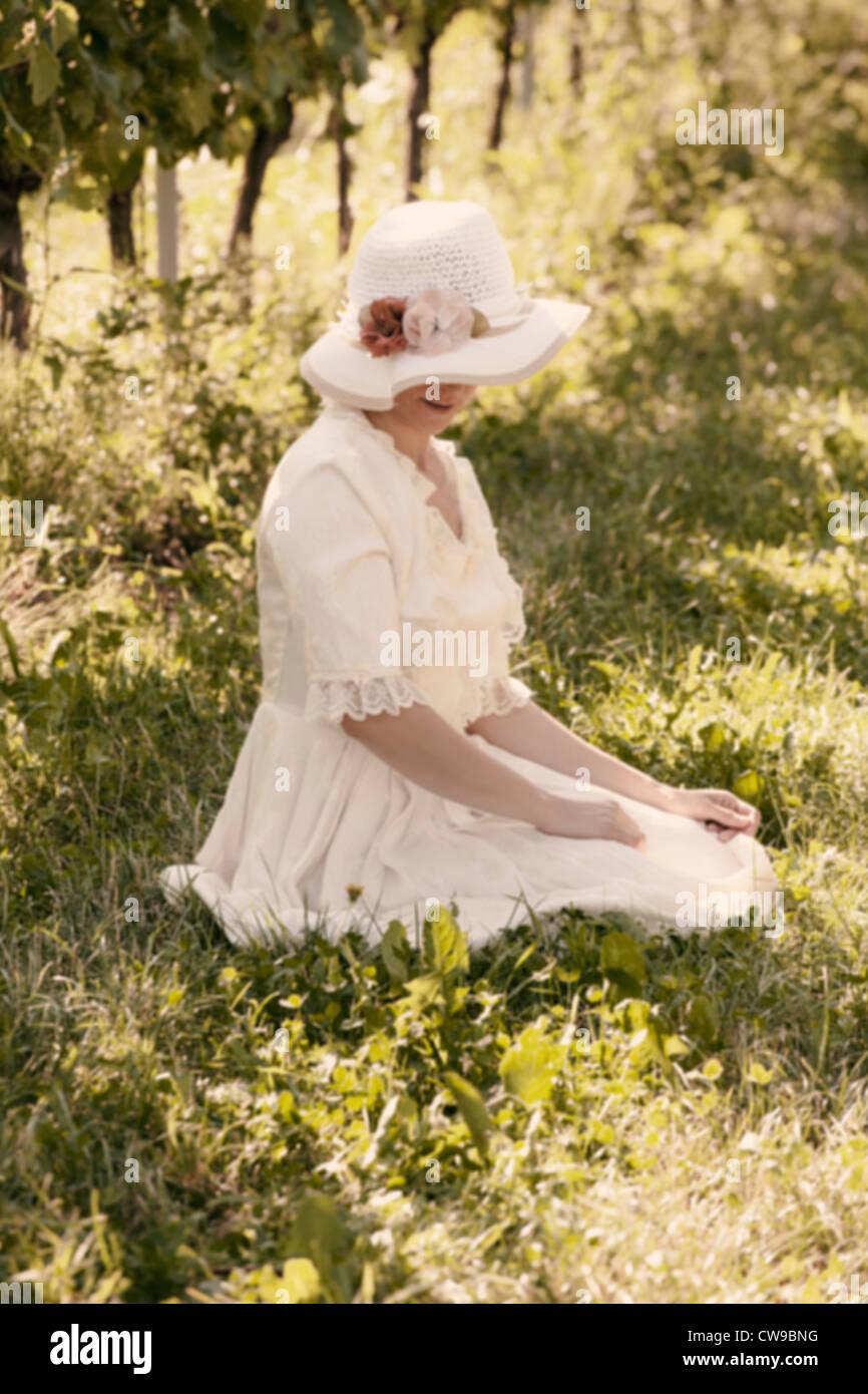 Una mujer en un vestido Victoriano blanco sentado en el pasto entre viñas Imagen De Stock