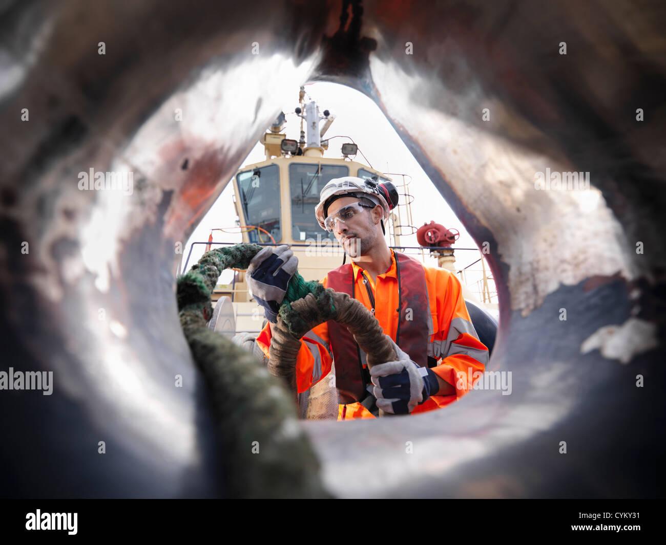 Trabajador de remolcadores tirando de la cuerda en la cubierta Imagen De Stock