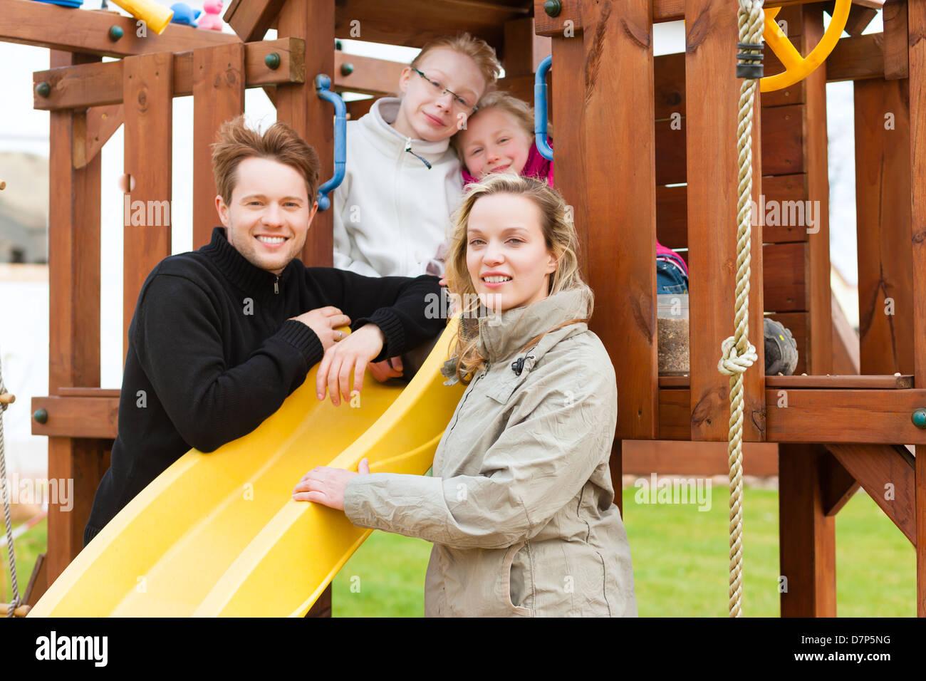 Familia joven en el patio de recreo, los niños sentados en un marco ...