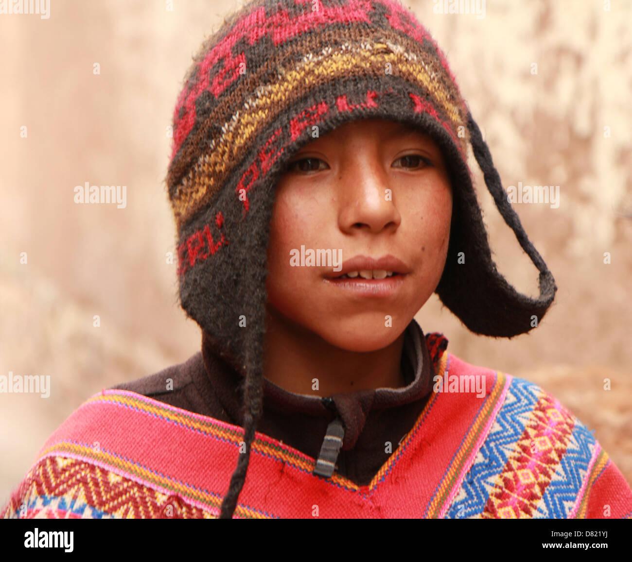 Un niño Quechua lleva un chulo tradicional sombrero y poncho en las calles  de Cusco 3b9e04e7d30