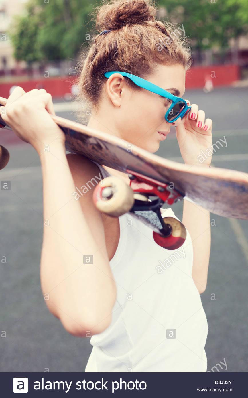 Biautiful joven mujer en azul gafas de sol de pie en el patio con un monopatín en sus manos en el día. Imagen De Stock