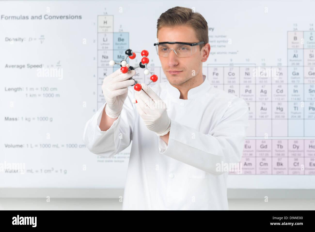 close up de guapo cientfico caucsica vestida de blanco uniforme estudia la estructura molecular con tabla peridica en segundo plano
