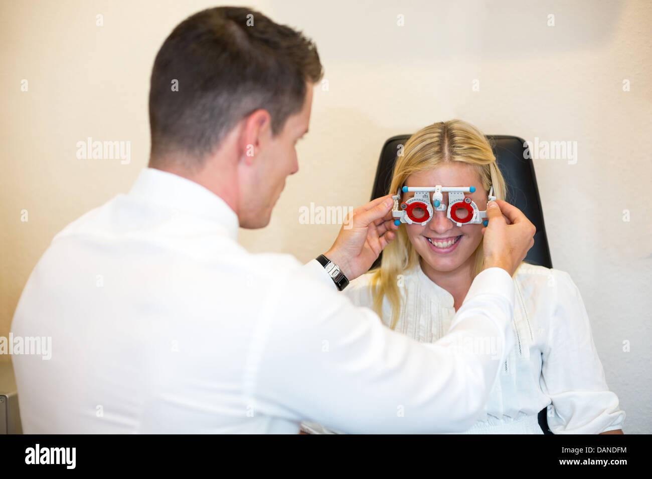 Cliente en una óptica gafas intentando prueba en un marco de prueba ...