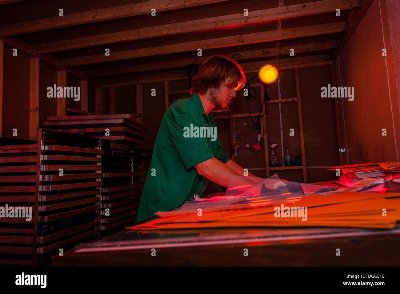 Hombre trabajando en el cuarto oscuro en el taller de serigrafía ...