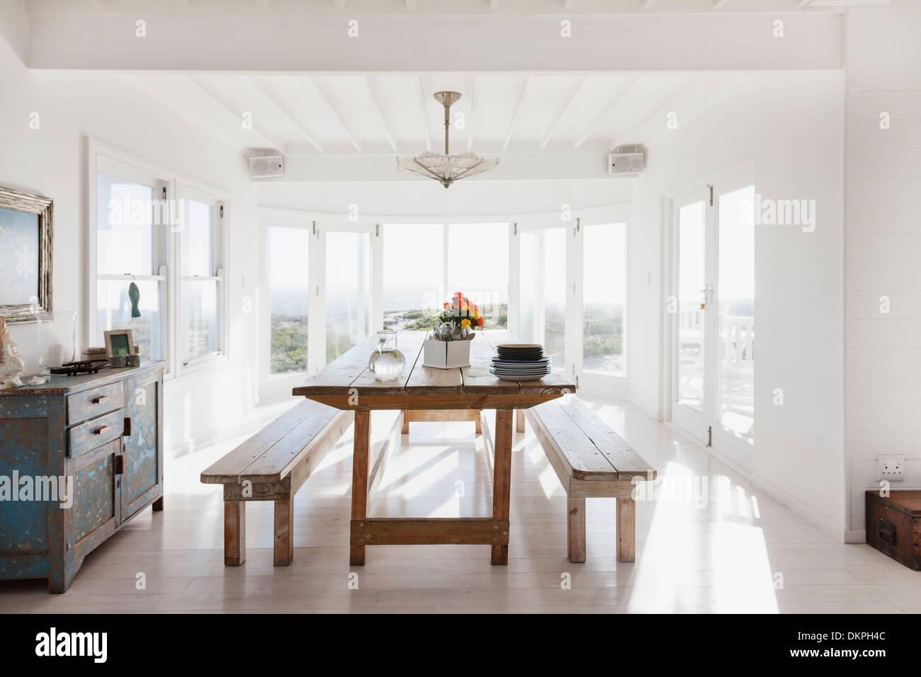 Mesa y bancos de madera en el soleado comedor Foto & Imagen De Stock ...