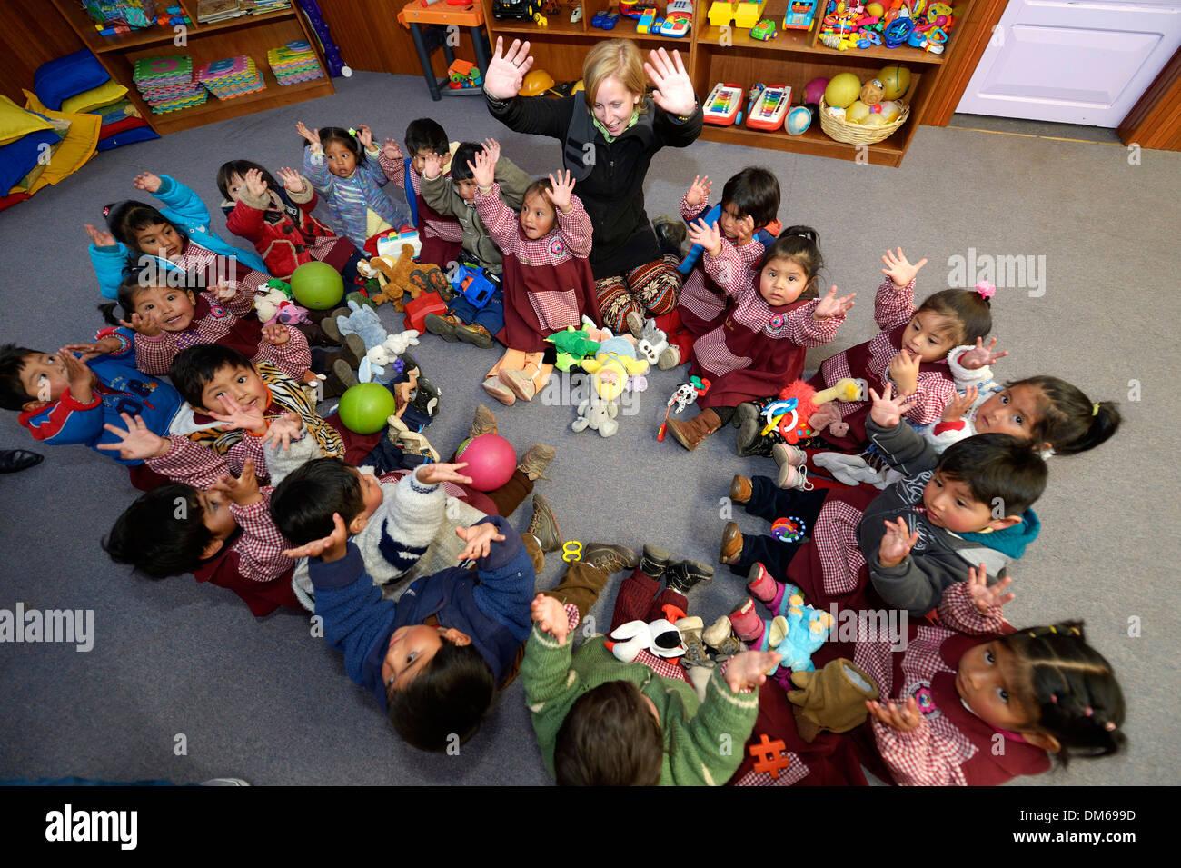 Los niños sentados en el suelo en un círculo en un jardín de ...