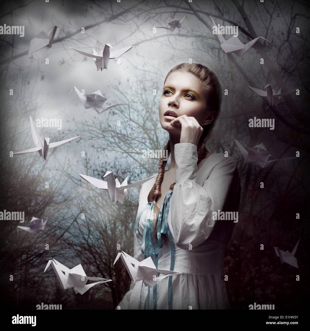 La inspiración. Mujer con origami cisnes blancos volando en oscuro bosque místico Imagen De Stock