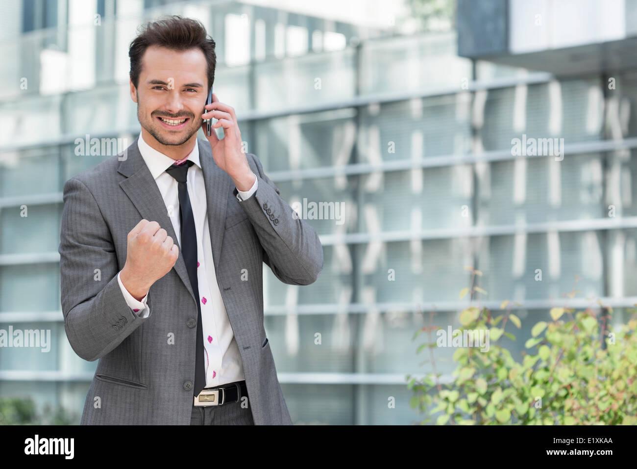 retrato del joven empresario exitoso utilizando teléfono celular