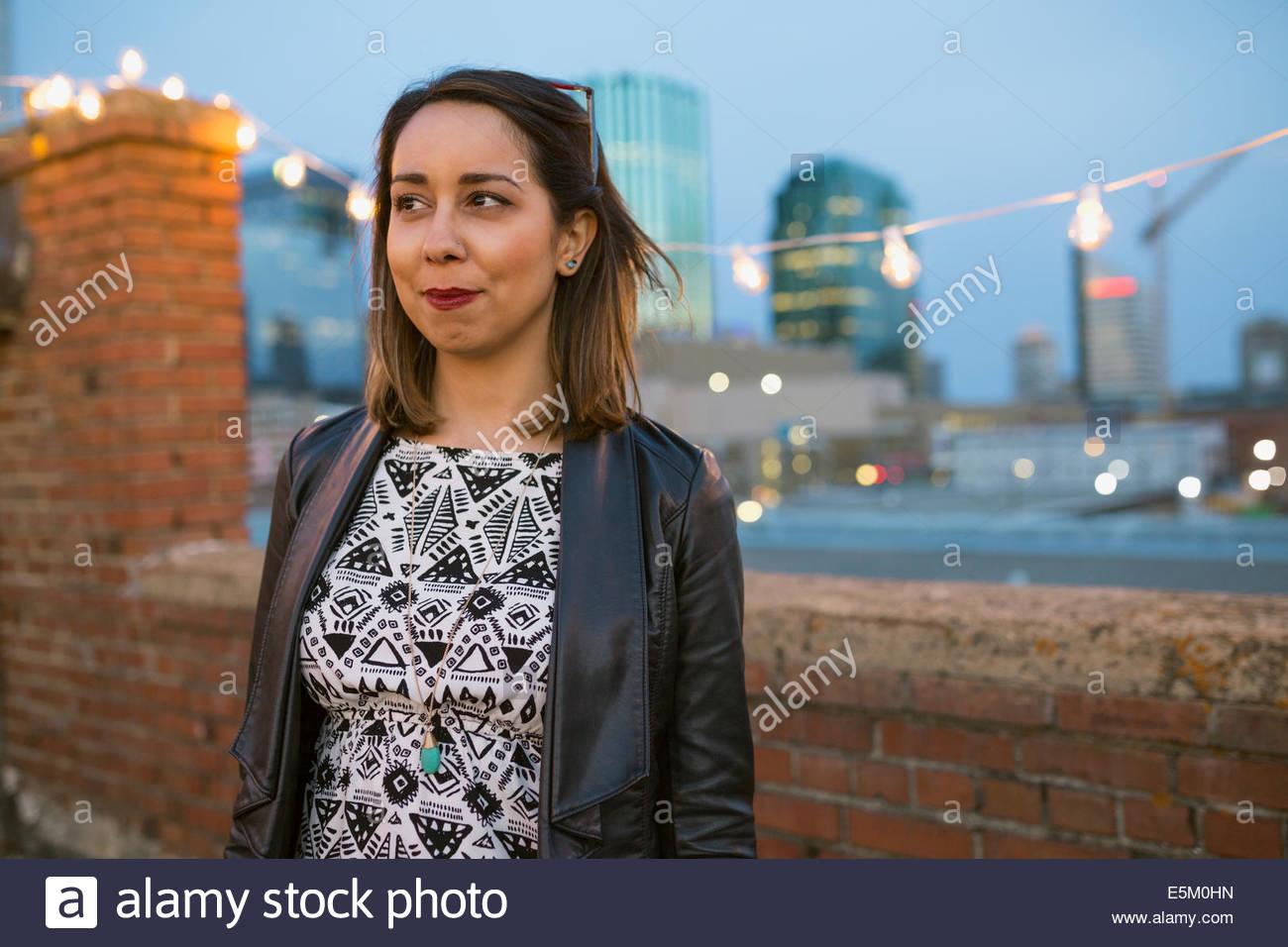 Mujer sonriente mirar lejos en la azotea urbana Imagen De Stock