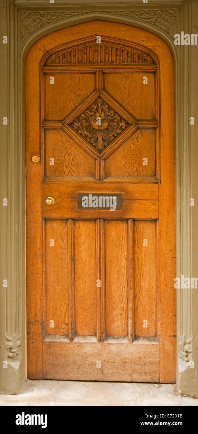 Puerta de madera marrón dorado con arcos superiores y diseños ...