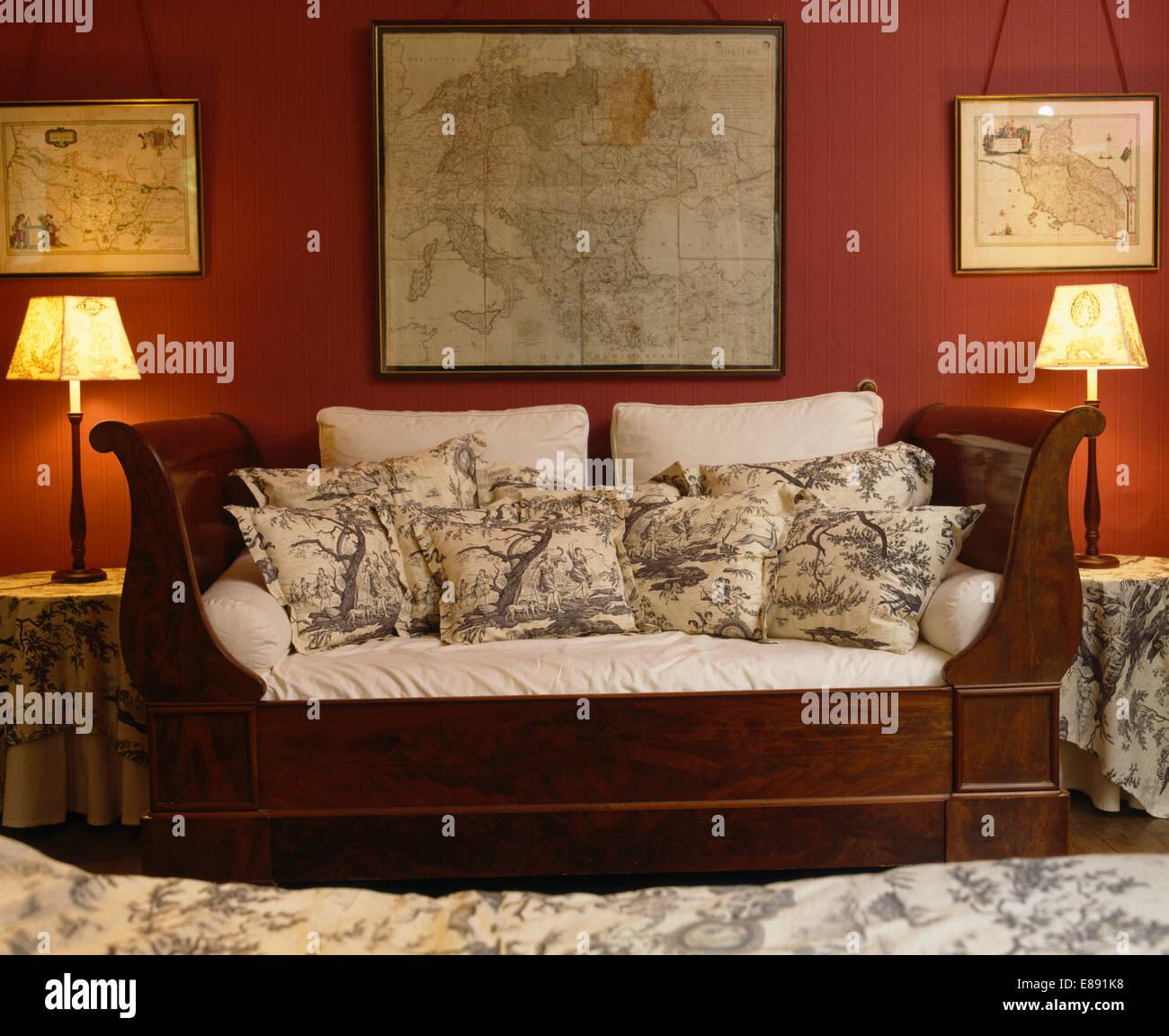 Mapas enmarcados en pared sobre sofá con cojines apilados en rojo ...