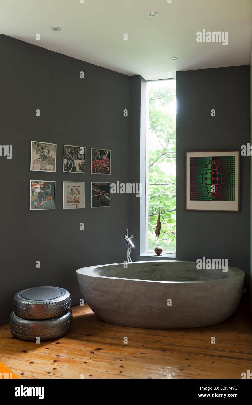 Gran bañera de hormigón gris crittal en habitación con ventanas. El ...