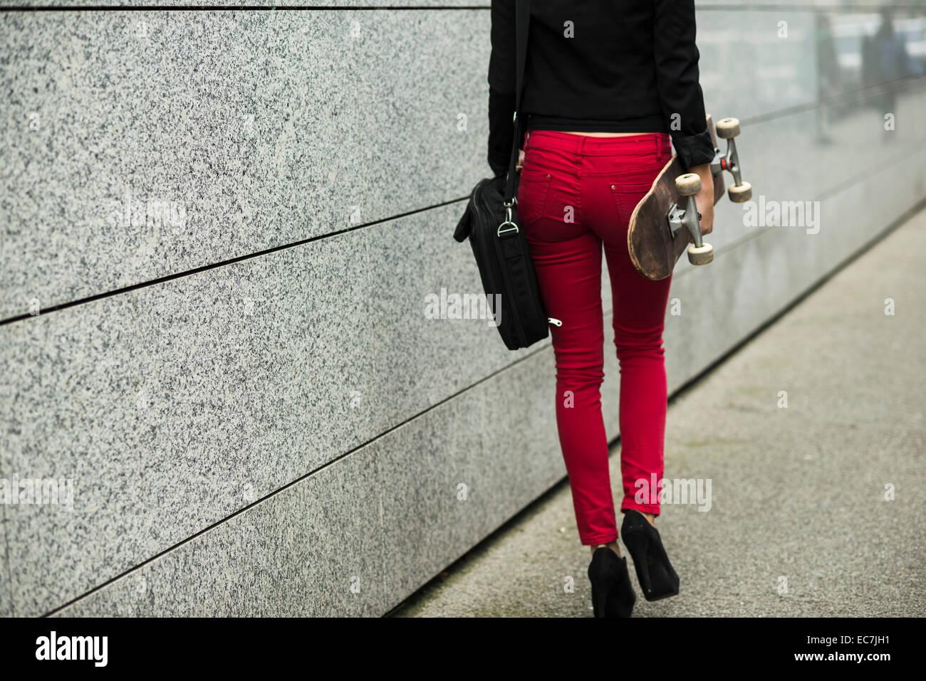 Mujer joven con bolsa y skate pantalones vestidos de rojo 8041c8599ff