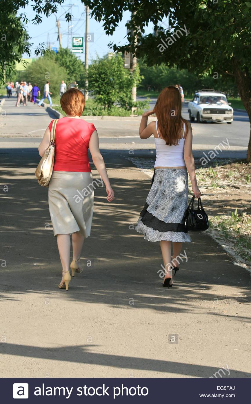 Dos Mujeres En Vestidos Caminando En La Acera Con Su Espalda A La