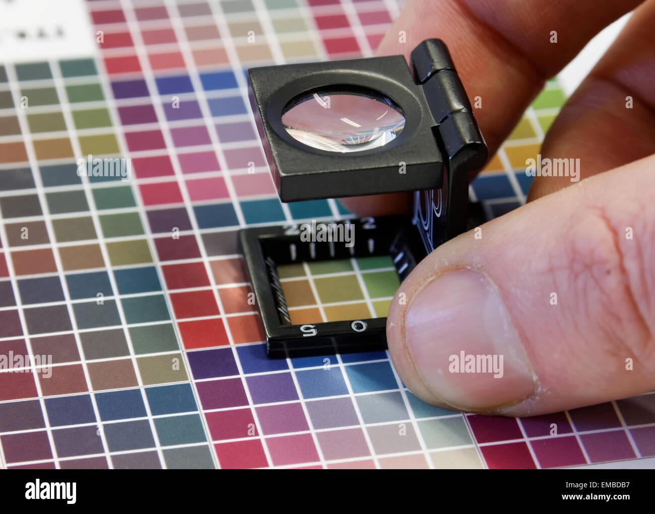 Close-up de una lupa en coloridos, prueba de impresión de inyección ...