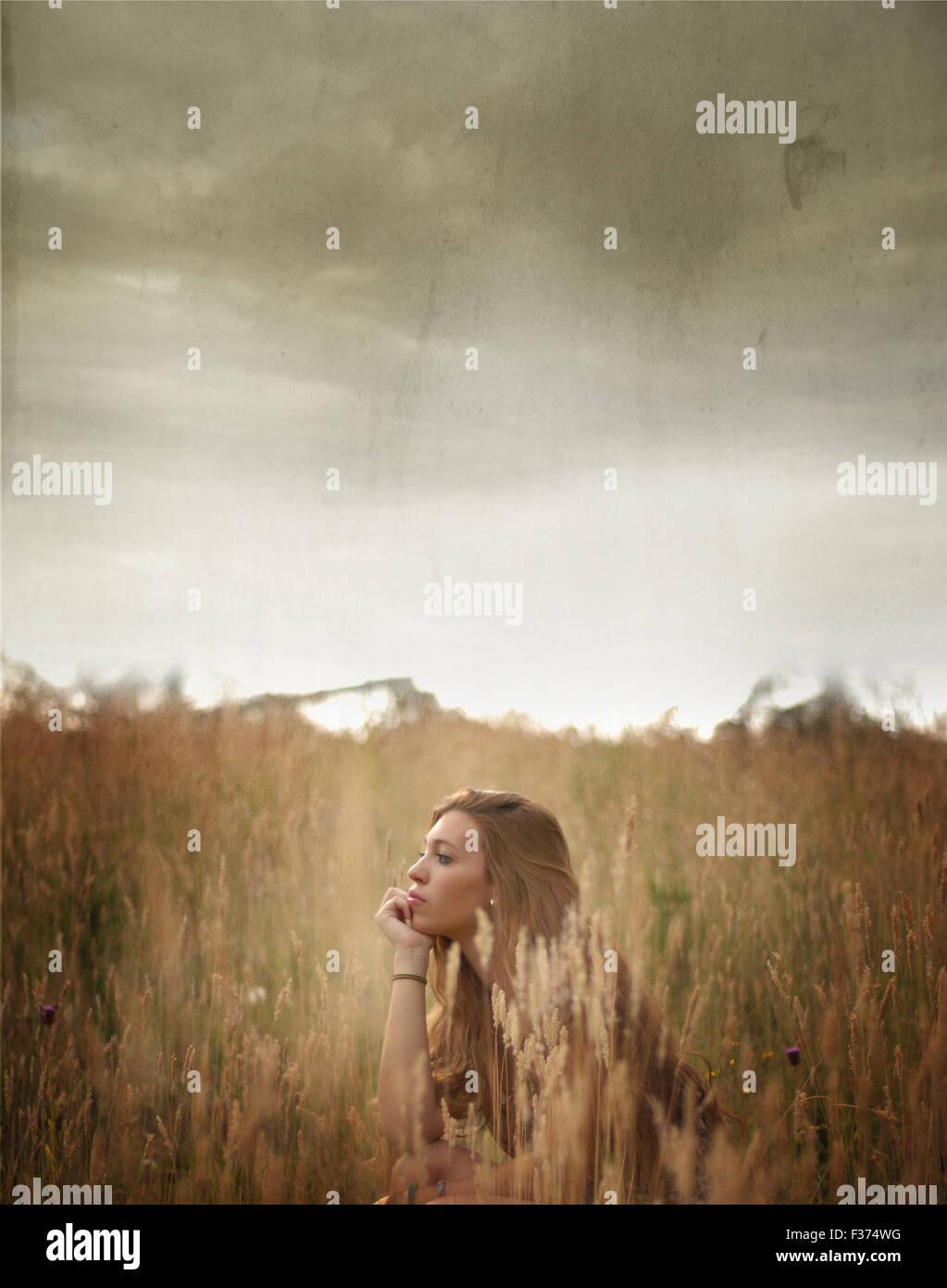 Chica sentada entre campos con un cielo tormentoso Imagen De Stock