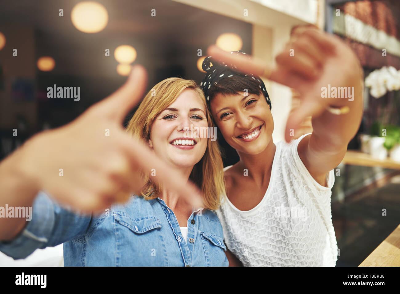 Las mujeres jóvenes vivaces enmarcar sus rostros con un dedo el ...