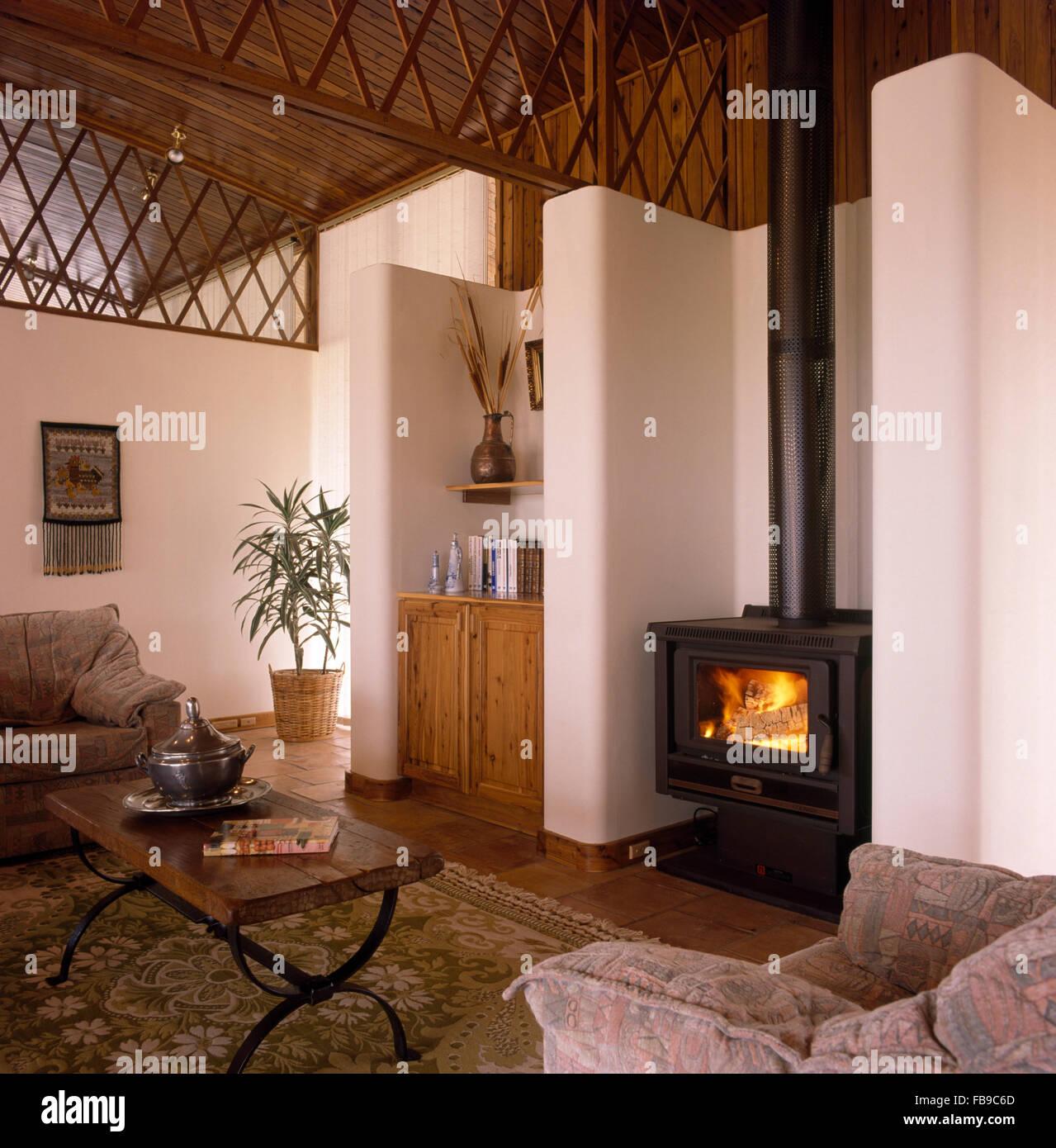 Estufa de leña en la sala de estar abierta con calados de madera ...