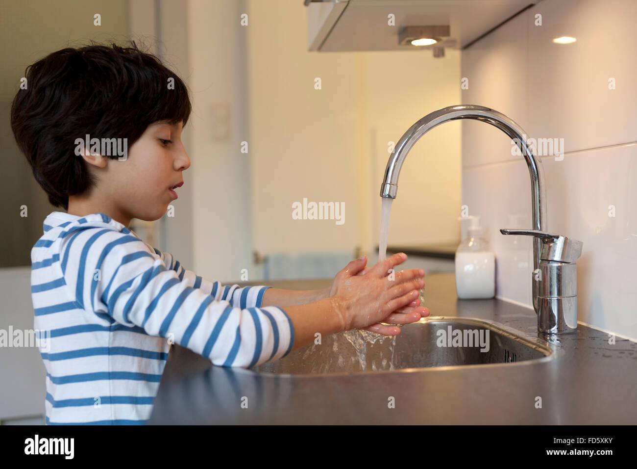 Boy washing im genes de stock boy washing fotos de stock for Lavado de manos en la cocina