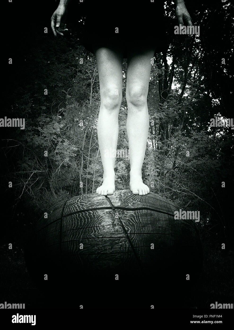 Mujer de pie en la parte superior del objeto de madera circular Imagen De Stock