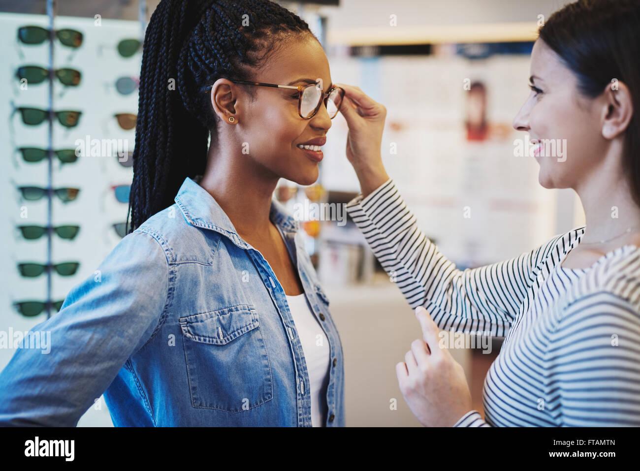 Optometrista ayudando a un cliente para tratar de África bonitas y ...
