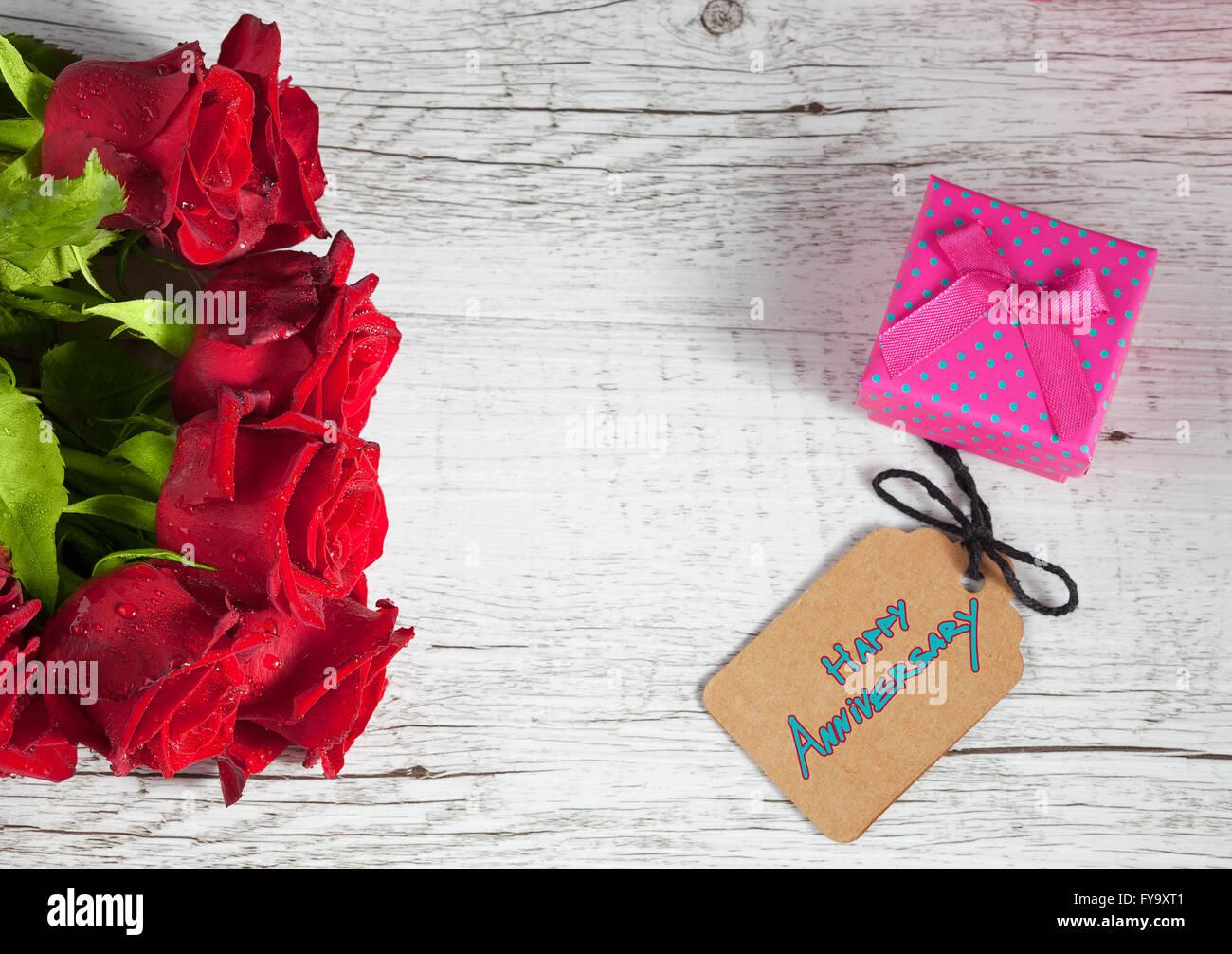 feliz aniversario el texto con la pequeña caja de regalo y rosas