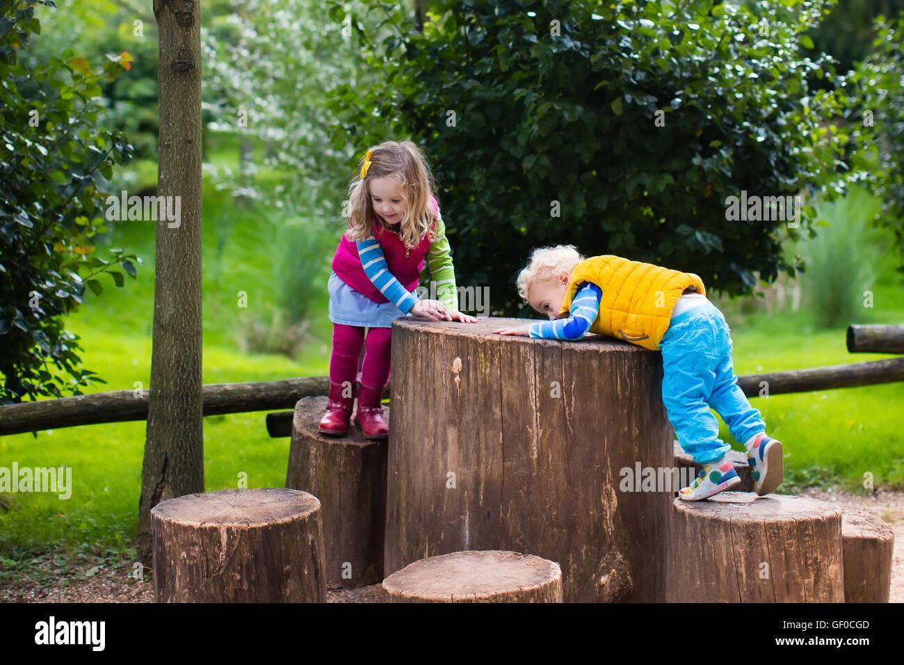 Chico y chica escalada en un patio de madera en un parque. Los niños ...