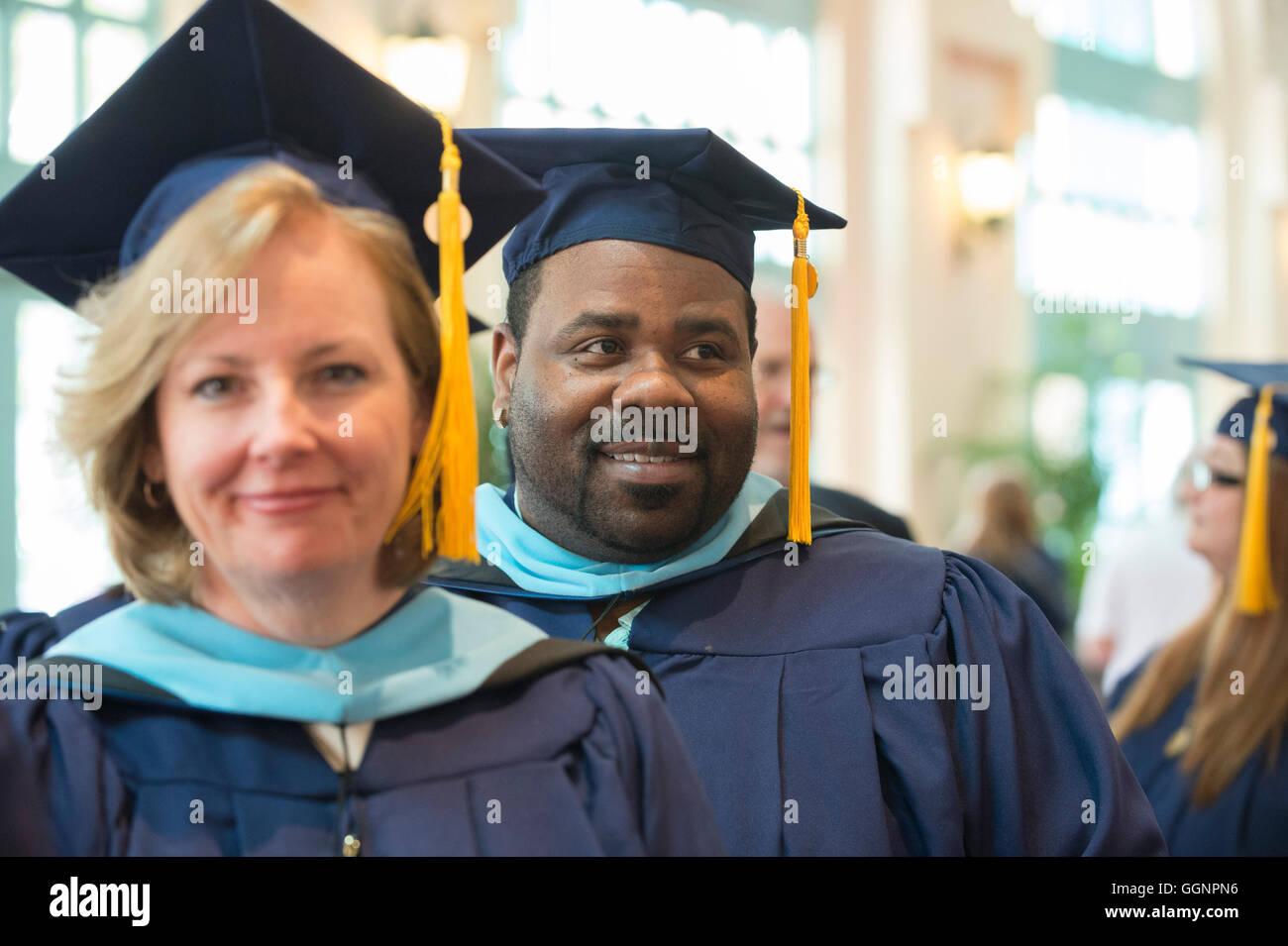 los candidatos de graduación en caps y batas esperar western