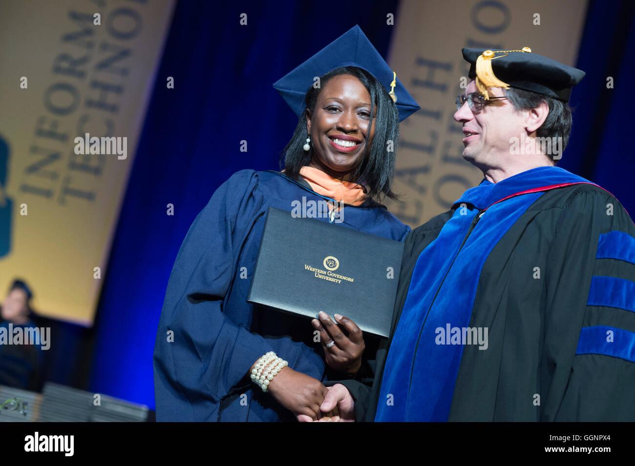 candidato de graduación en toga y birrete recibe diploma en western