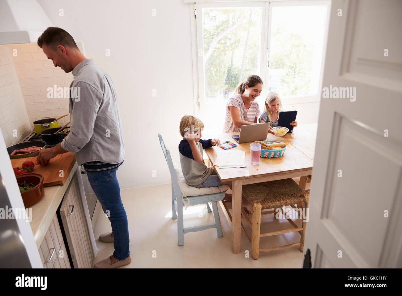 Papá y mamá cocina con niños en la mesa de la cocina Foto & Imagen ...