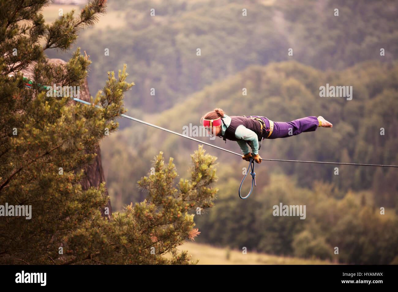 OSTROV, REPÚBLICA CHECA: una hembra slackliner muestra off en el alambre alto. En vestirse de traje para alquiler Imagen De Stock