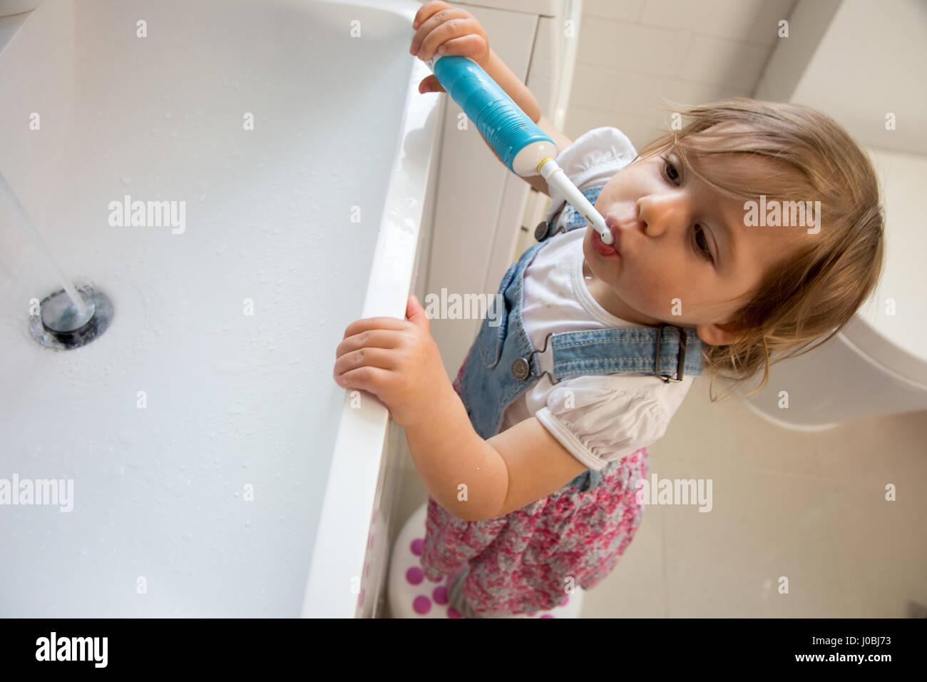 Niña Niño cepillarse los dientes con un cepillo de dientes eléctrico de  adultos. Ella es de 16 meses de edad 83d78abc38f5
