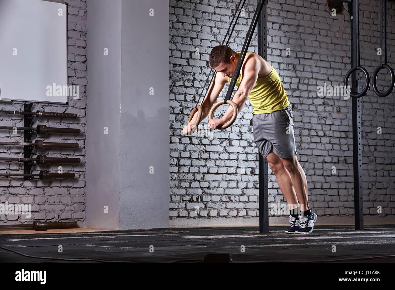 Atlético joven hombre en el sportwear entrenamiento en el gimnasio con anillos de cross fit contra la pared Imagen De Stock