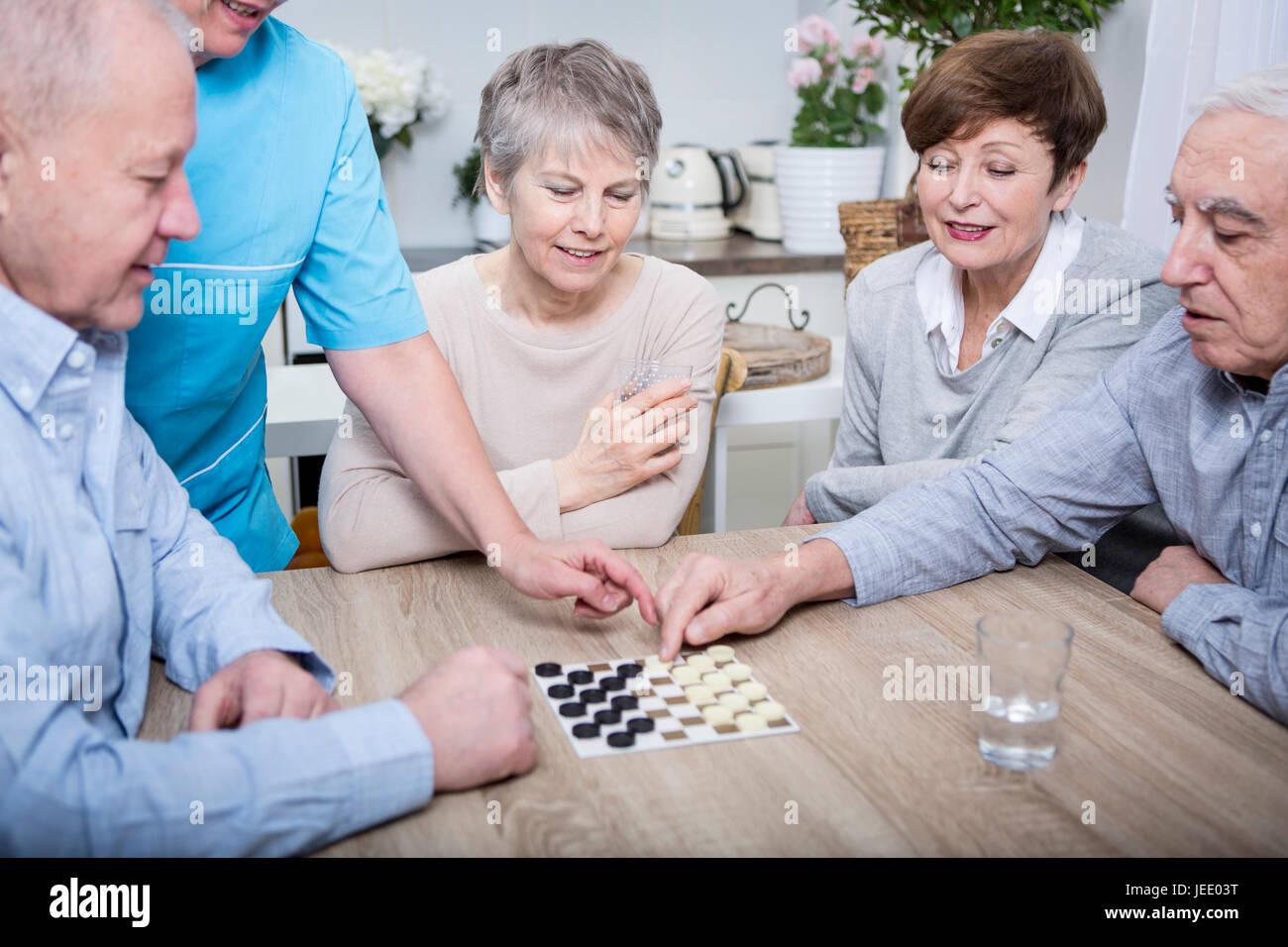 Enfermera Ayudando Con Una Noche De Juegos Para Ancianos Foto