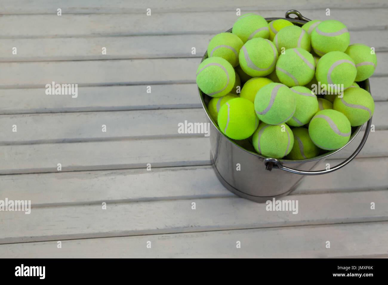 5a58f18a1c Un alto ángulo de visualización de las pelotas de tenis en la cuchara  metálica sobre la mesa de madera blanca