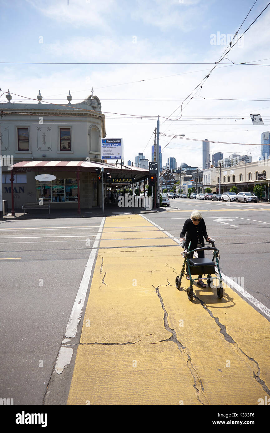 Una anciana con un andador cruza una amplia calle en Melbourne ...