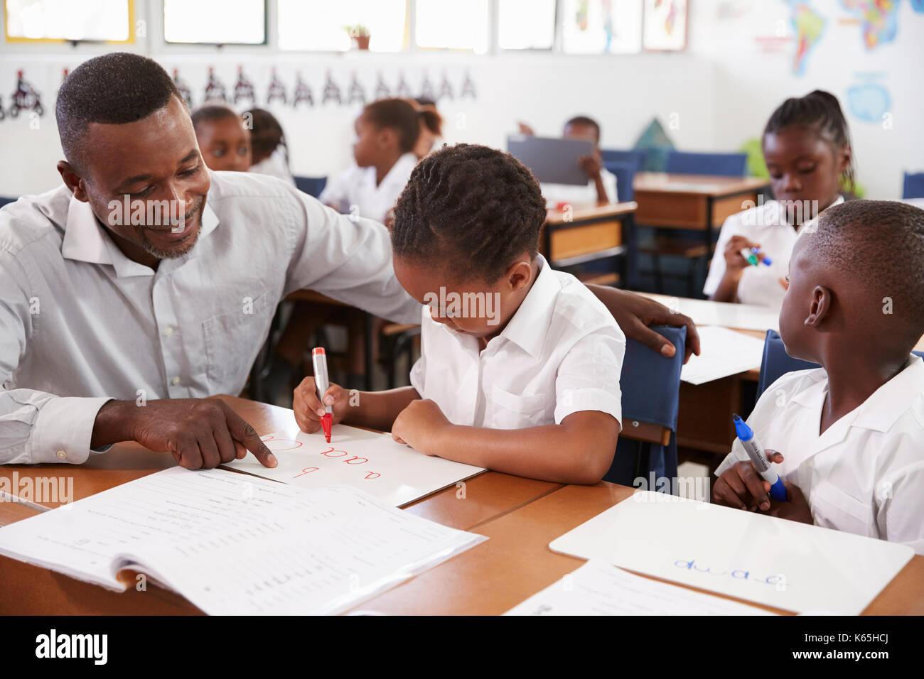 Profesor ayudando a niña de la escuela elemental en su pupitre en la clase d8068acbfbb