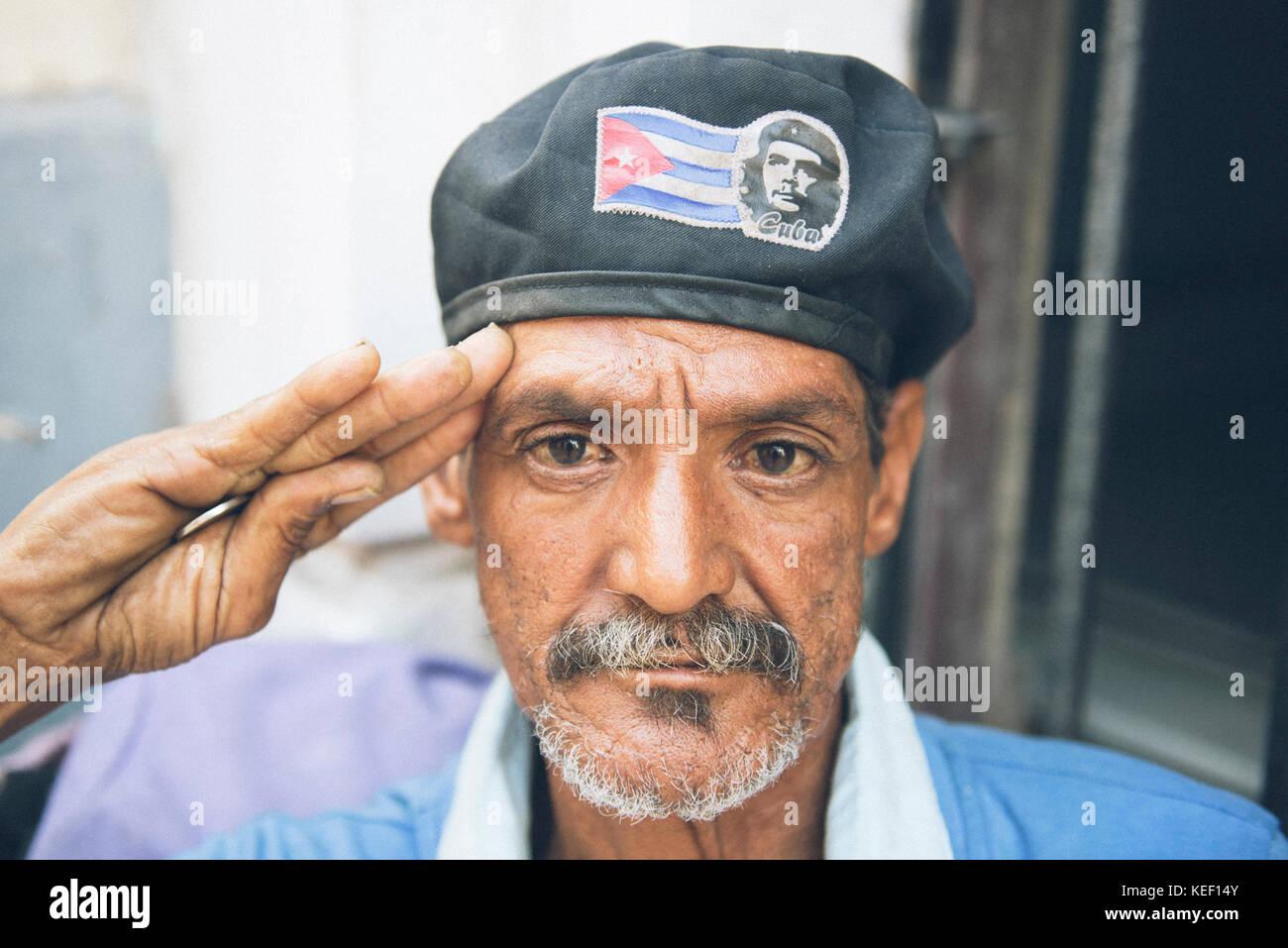 f477f6ef6d129 Patriota cubana hombre saluda como un soldado mientras llevaba una gorra  con una bandera cubana y la imagen del Che Guevara.