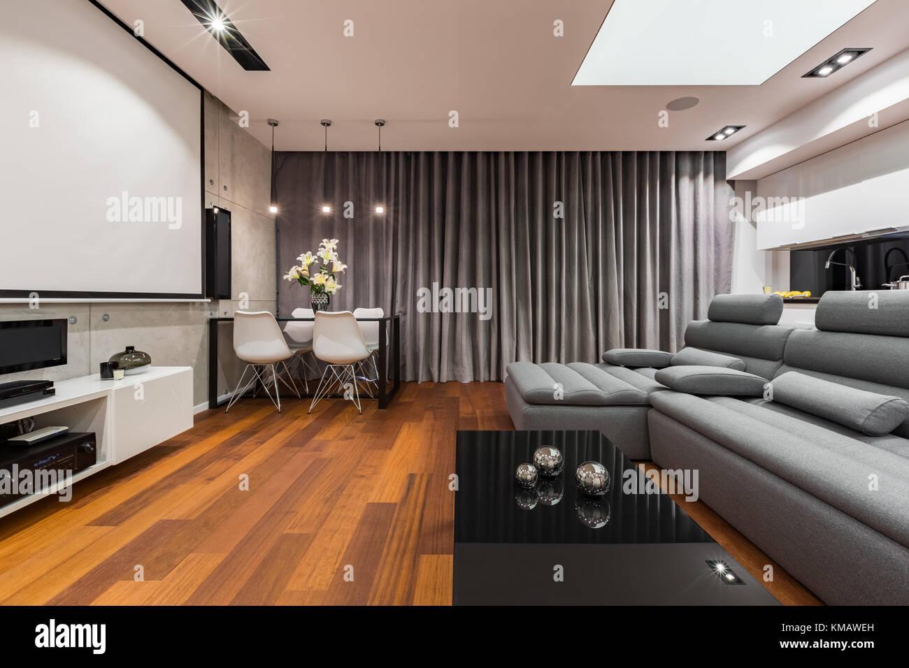 Apartamento gris y blanco con pantalla para proyector, sofá, mesa de ...