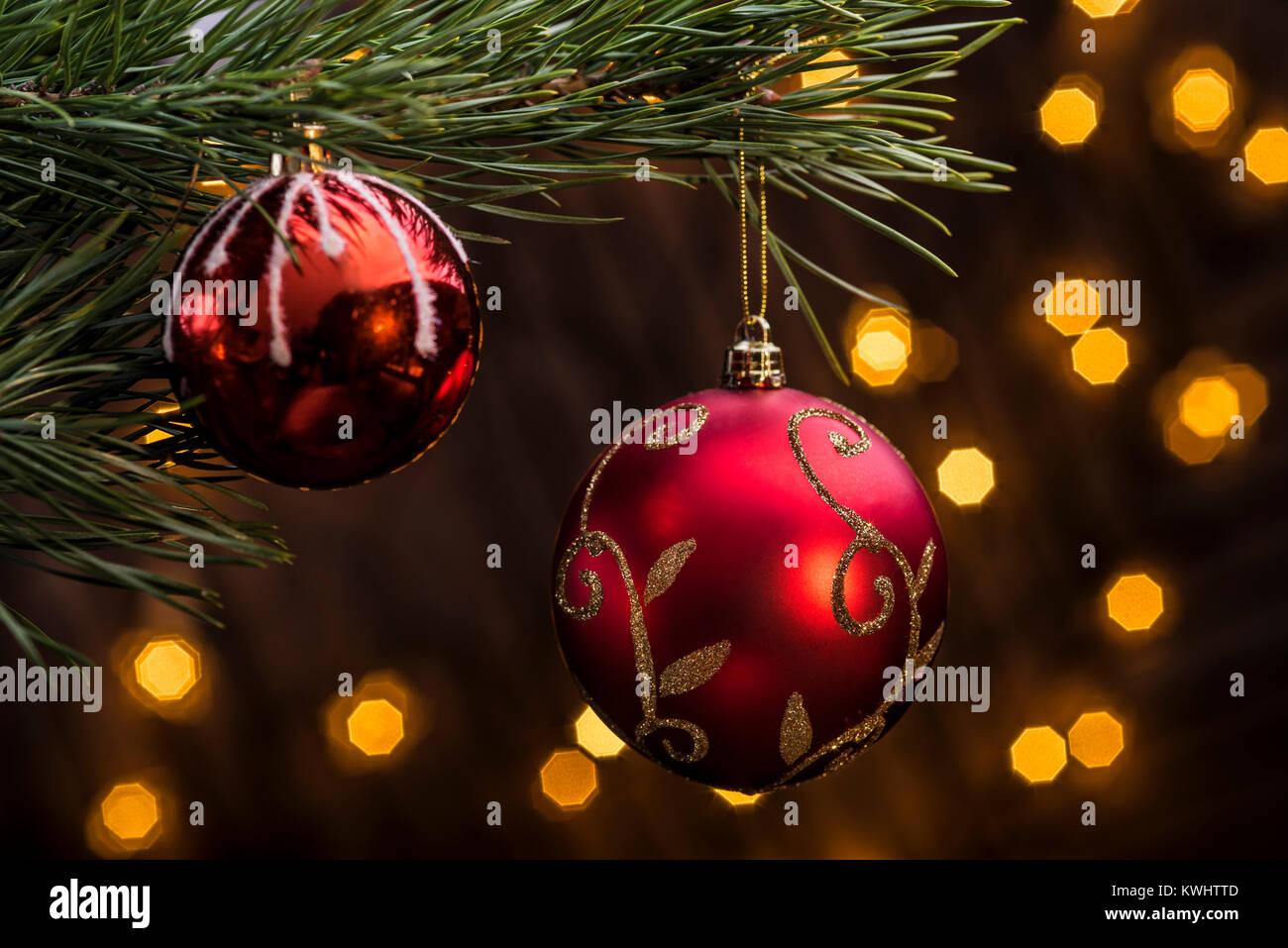 e43c0a1ec71 Bola roja colgando del árbol de navidad con luces festivas de fucus en  segundo plano.