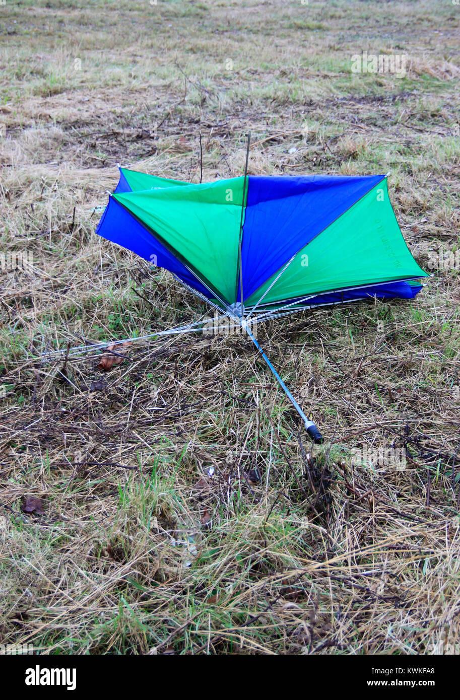 Brillantemente coloreado azul y verde paraguas rotos en el páramo ...