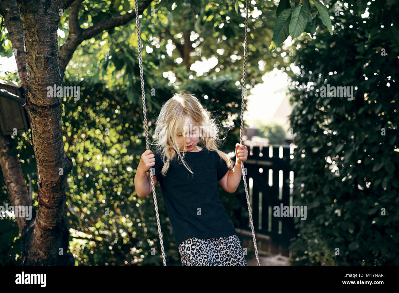 Adorable pequeño chica rubia colgando de un árbol columpio mientras ...