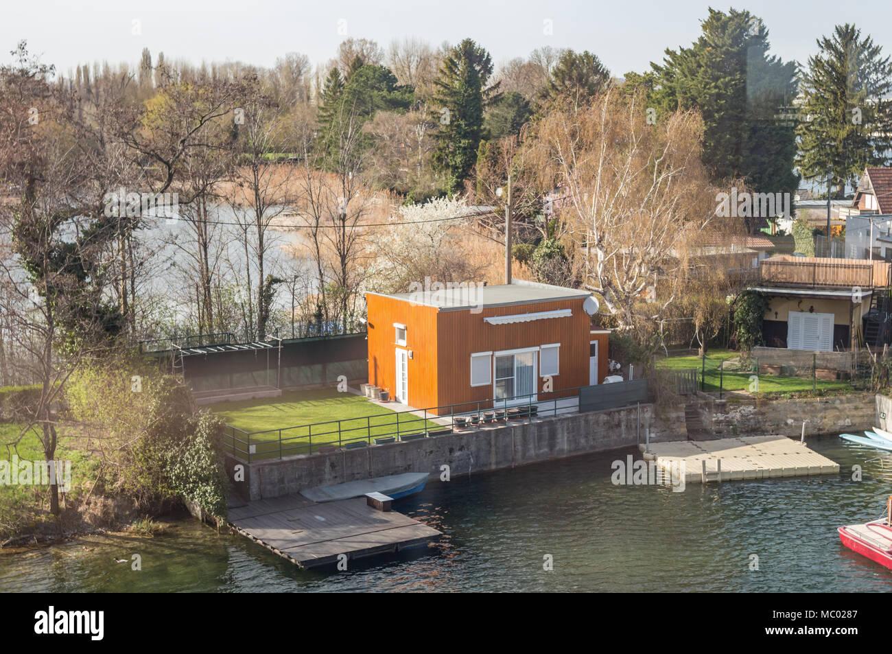 Pequeña casa de bastidor de metal y madera, cerca del lago dock ...