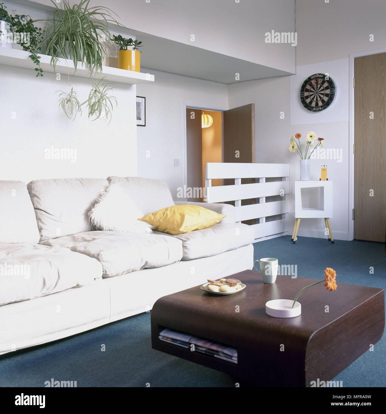 moderna sala blanca alfombra azul sofá mesita estantería foto